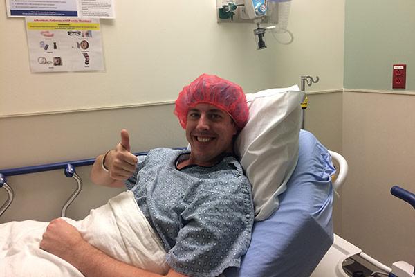 Matt Cross giving thumbs up in the hospital