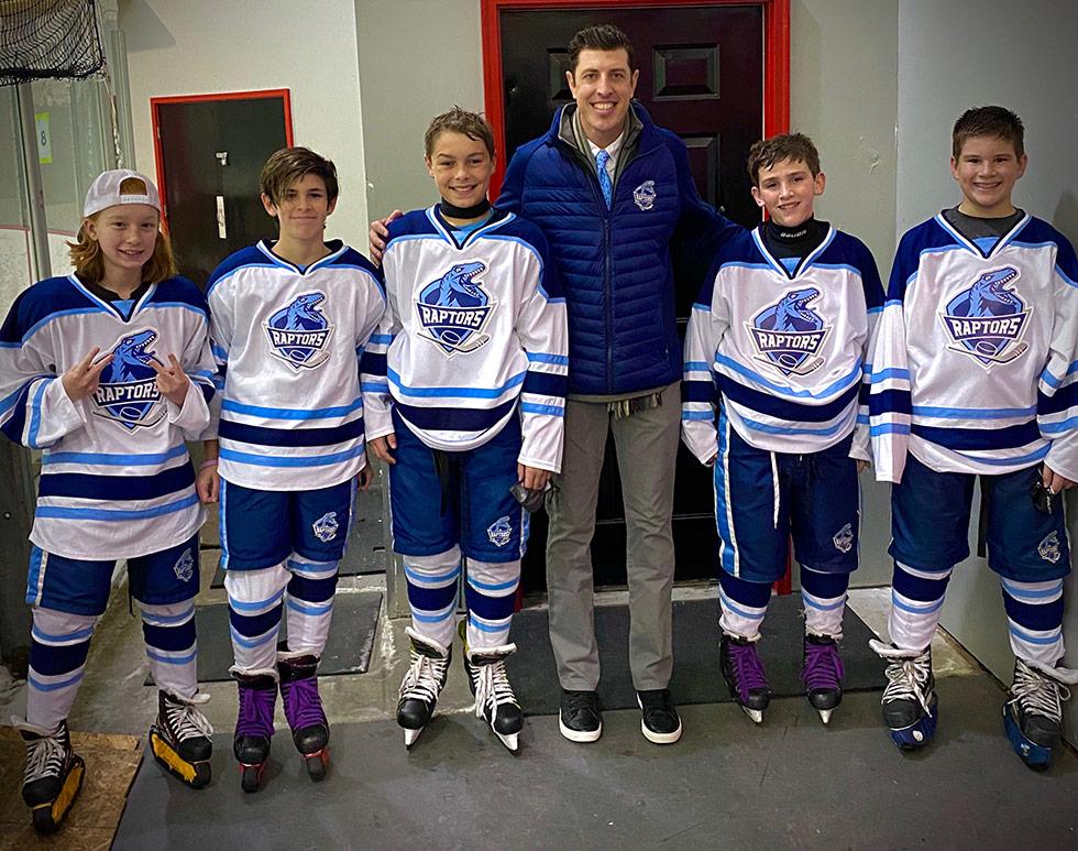 Matt Cross with kids on hockey team in uniform